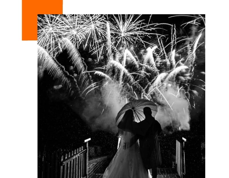 A bride and groom watch a fireworks display at their wedding